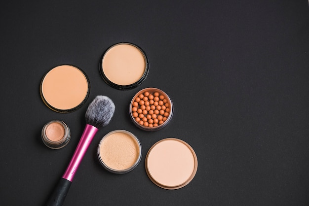 Makeup products with brush on black backdrop