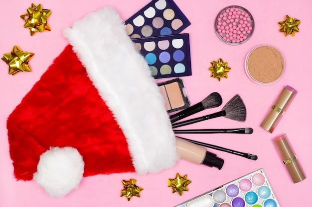 サンタの帽子とギフト用のリボンが付いたメイクアップ製品クリスマスと新年のプレゼントとしてのメイクアップ化粧品