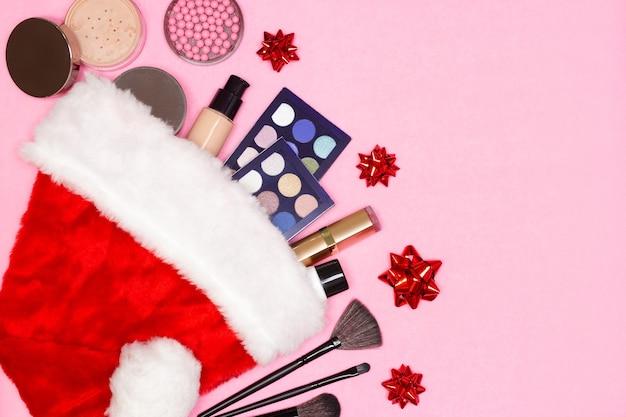 サンタの帽子をかぶった化粧品上面図コピースペースクリスマスプレゼントとしての化粧品