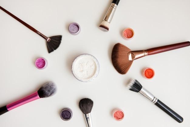 Набор для макияжа. кисти, пудра, пигменты на белом фоне. профессиональные средства и тени для макияжа глаз.