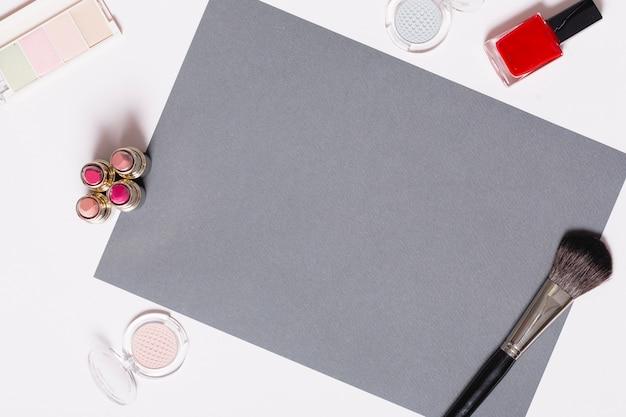 Forniture per il trucco intorno al foglio di carta grigia