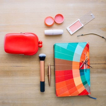 Makeup supplies and bright notebook