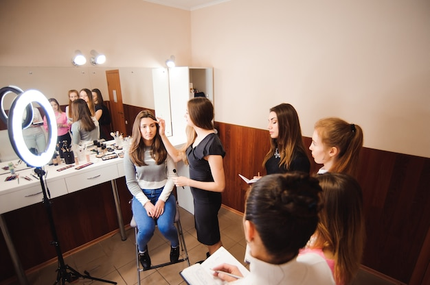 Makeup teacher with her student girls. makeup tutorial lesson at beauty school. makeup master class.