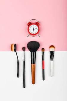 메이크업 시간 개념. 메이크업 브러쉬. 평평한 화장 용 화장품 및 액세서리. 빨간색 알람 시계와 색상에 화장품 조성. 메이크업 컨셉입니다.