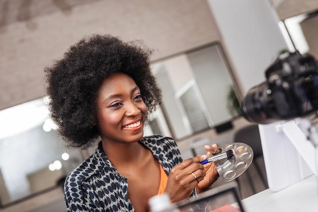 メイクアップ時間。化粧をしながらパレットからコンシーラーを取る珊瑚の口紅を持つかわいい浅黒い肌の女性