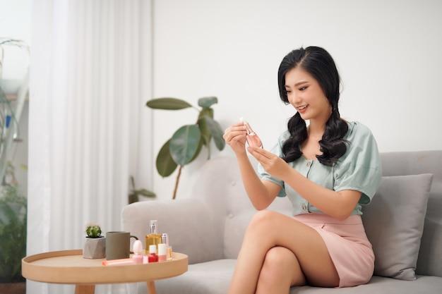 메이크업 시간. 거실에서 화장을 하 고 젊은 아시아 여성