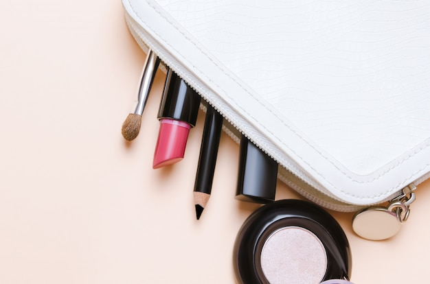 Makeup tools and cosmetics on beige background