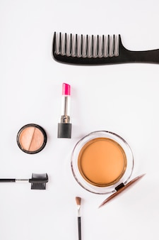 Makeup tools and cosmetics on white backdrop