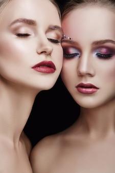 Макияж двух обнимающихся девушек, множество страз разной формы, красивый уход за гладкой кожей лица. косметический макияж на лице двух женщин крупным планом