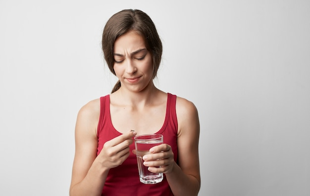 Makeup woman in red t-shirt holds glass of water pill medicine health problems.