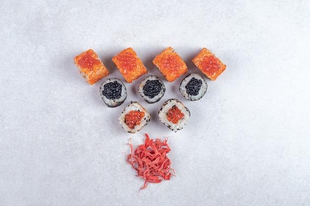 マキ、アラスカ、カリフォルニアの寿司は、白地に生姜のピクルスで巻かれています。