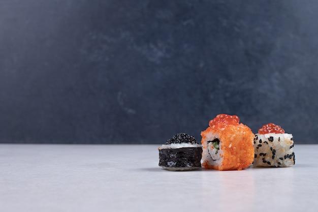 マキ、アラスカ、カリフォルニアの寿司が白いテーブルの上で転がります。