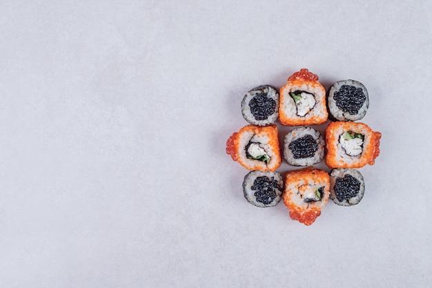 マキとカリフォルニアの寿司は白い背景に巻かれています。