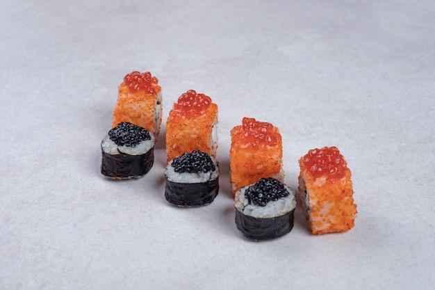 マキとカリフォルニアの寿司は白い表面に巻かれています。