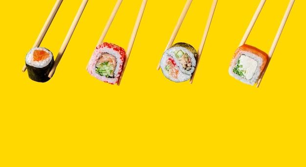 Маки, рулетики из калифорнии, инь-ян и филадельфия на палочках для еды на желтом фоне