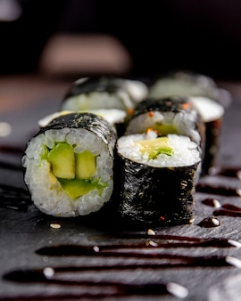Maki roll with avocado served with sauce
