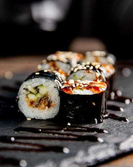 Maki roll with cucumber served with sauce and sesame seeds