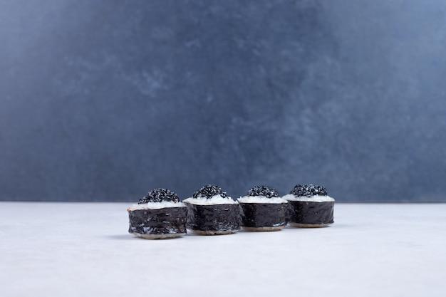 白いテーブルに黒いキャビアで飾られた巻き寿司。