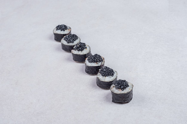 Maki rolls decorated with black caviar on white background.