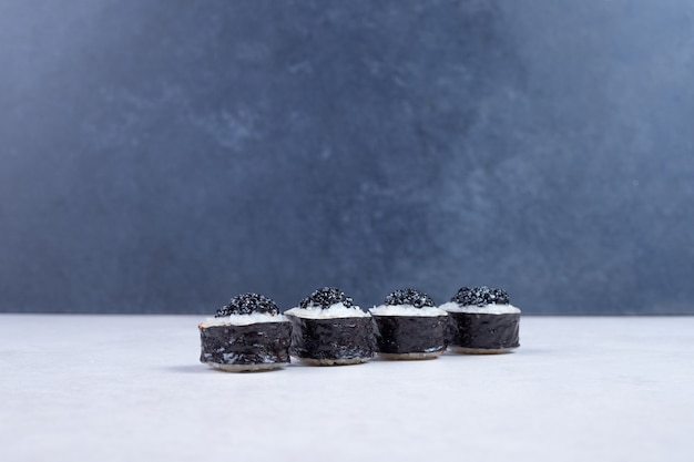 Maki rolls decorated with black caviar on white table.