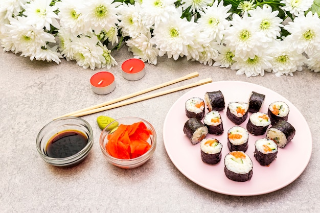 Маки роллы с имбирем, васаби и соевым соусом, свечами и цветами