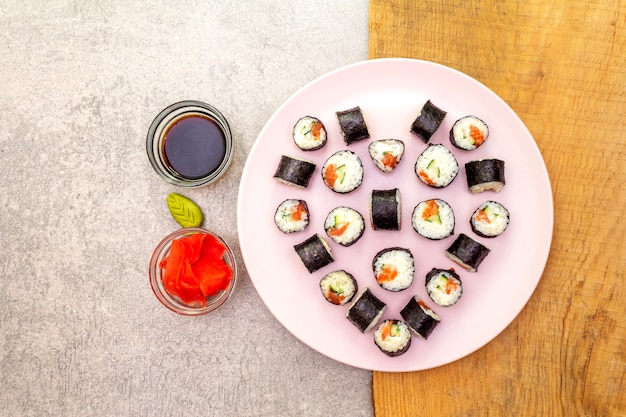 Maki rolls with ginger, wasabi and soy sauce on rosy plate
