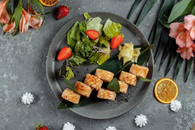 Маки суши - ролл из сливочного сыра, клубники, авокадо и жареного лосося. летние сезонные суши-роллы.