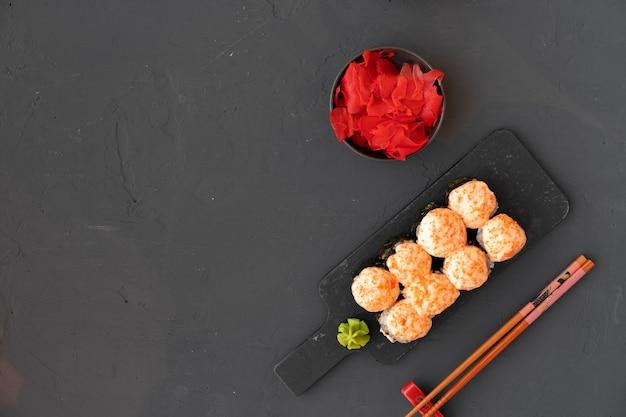 Маки суши на черной каменной тарелке сверху