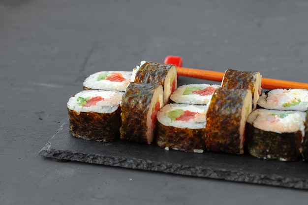 Maki sushi roll served on stone plate on gray