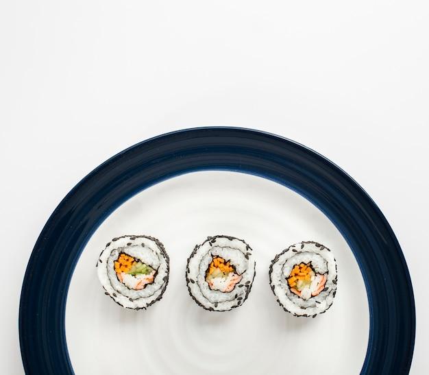 Rotoli di sushi di maki sul piatto bianco e blu