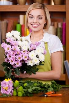 Делаем красивый букет цветов. красивая молодая женщина со светлыми волосами в фартуке, устраивает цветы и смотрит в камеру