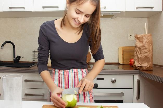 ケーキを作る。女の子はキッチンでナイフで皮から緑のリンゴを皮をむきます。