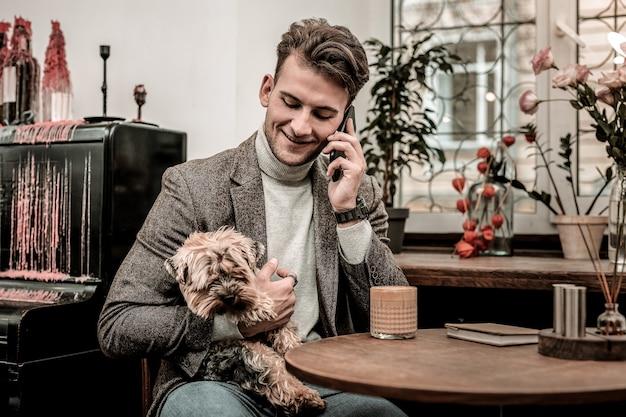 전화 걸기. 전화를하는 동안 개를 안고 남자