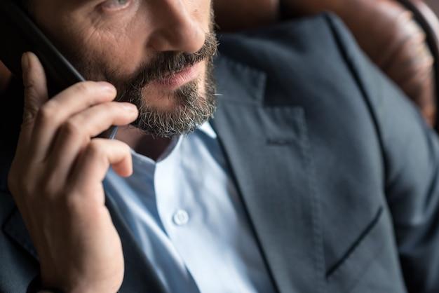 Звонок. приятный красивый бородатый мужчина держит мобильный телефон и подносит его к уху во время телефонного звонка