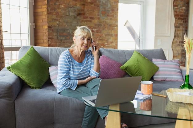 Звонок. старшая женщина учится дома, получает онлайн-курсы, саморазвитие. кавказская женщина использует современные устройства для развлечения, обучения, тратить время на новую работу или хобби.