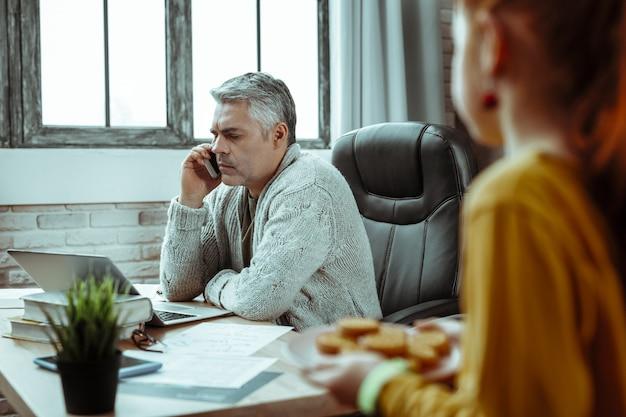 Звонок. серьезный зрелый мужчина прикладывает телефон к уху во время звонка