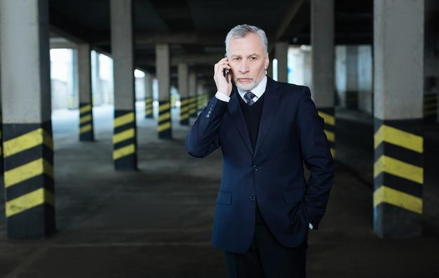 Звонок. серьезный красивый красивый бизнесмен кладет руку в карман и держит смартфон во время звонка