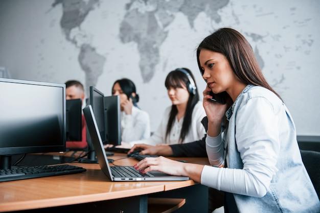 取り引き。コールセンターで働く若者たち。新しい取引が来ています