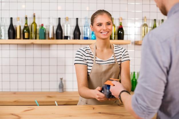 支払いをする。お金の端末を持って、支払いをしながら顧客を見ている陽気でフレンドリーな若い女性