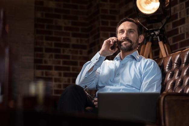 電話をかける。ソファに座って電話をかけながら笑っている嬉しい素敵なひげを生やした男