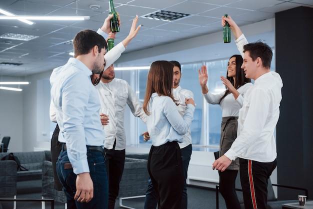 トーストを作る。モダンな照明付きのオフィスで飲み物を押しながら成功を祝うクラシックな服装の若いチームの写真