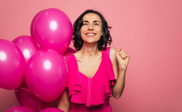 Загадывать желание. крупным планом фото счастливой девушки брюнетки в яркой одежде, которая с большой улыбкой смотрит вверх, держа воздушные шары в правой руке.