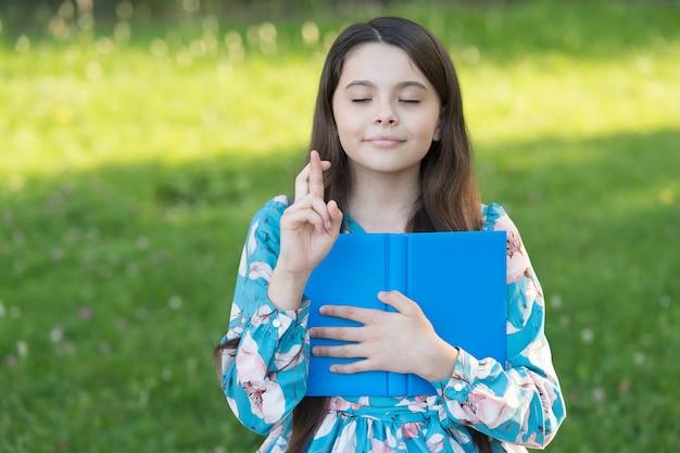Загадывать желание. маленький ребенок скрестил пальцы на удачу. маленькая девочка держит книгу в парке. следуй за своей мечтой. мечта и фантазия. летний отпуск. мечтайте маленькую мечту.