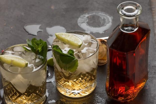 Приготовление алкогольного коктейля из рома, льда и лайма