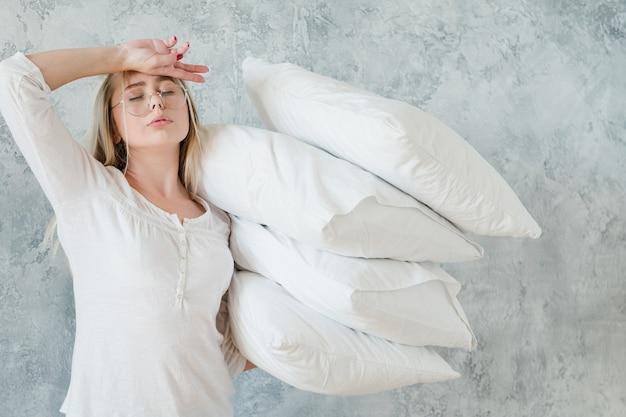 ベッドメイキング。朝の雑用の概念。枕の山を保持している疲れた女性。