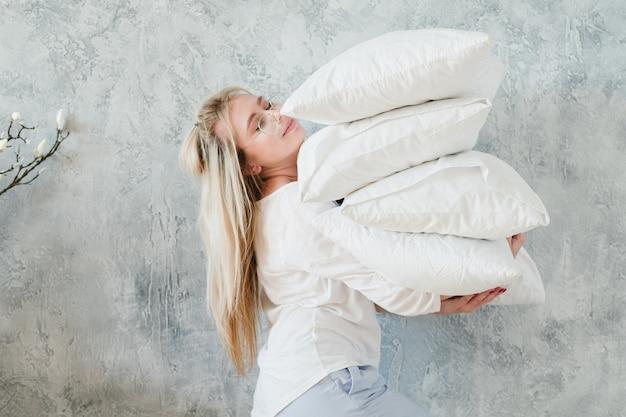 ベッドメイキング。朝の雑用の概念。枕の山を保持している女性