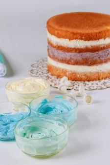パーティーケーキの装飾のための青と白のアイシングを作る。