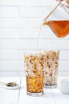 バブルティーを作る、白い木製のテーブルの背景にガラスのカップを飲むブラウンシュガーパターンにブレンドミルクティーを注ぐ、クローズアップ、コピースペース