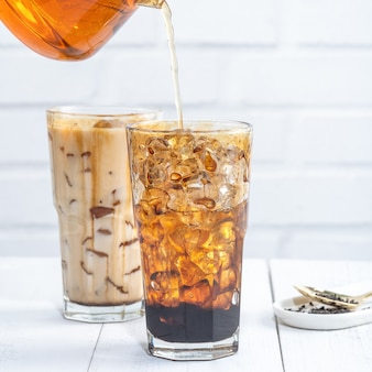 Making bubble tea, pouring blend milk tea into brown sugar pattern drinking glass cup on white wooden table background, close up, copy space