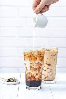 거품 차 만들기, 흰색 나무 테이블 배경에 갈색 설탕 패턴 마시는 유리 컵에 우유를 붓는.